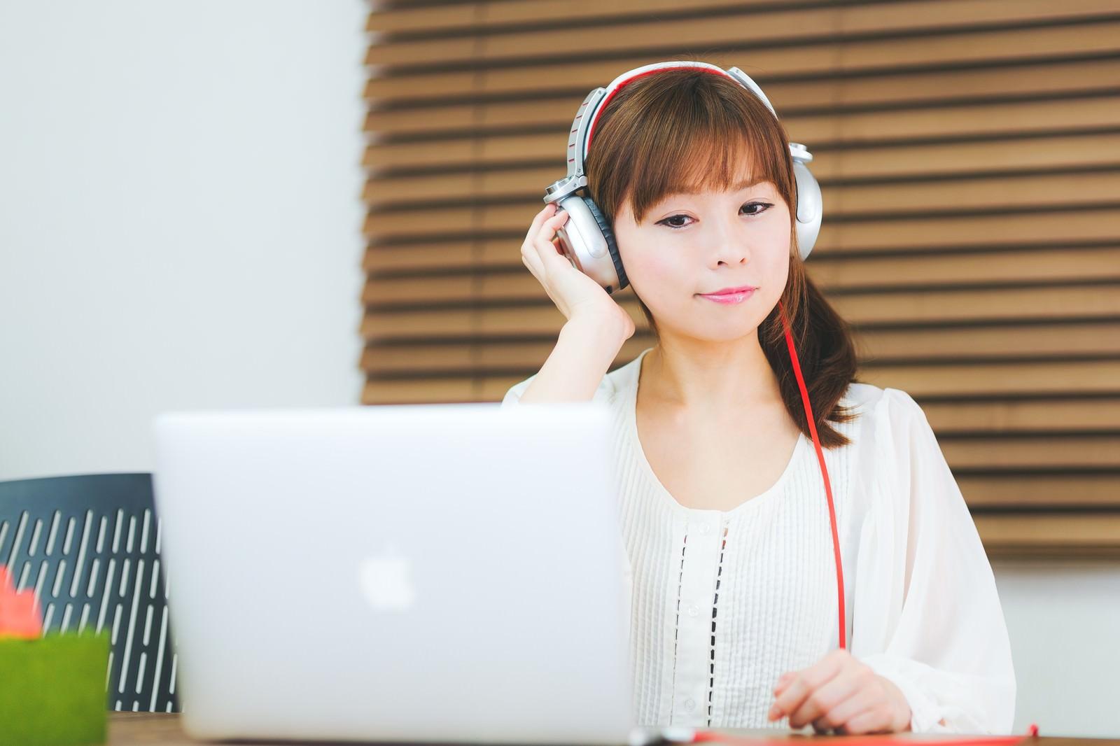 「ヘッドフォンで音楽を聴きながらノマドする女性」の写真[モデル:暢子]