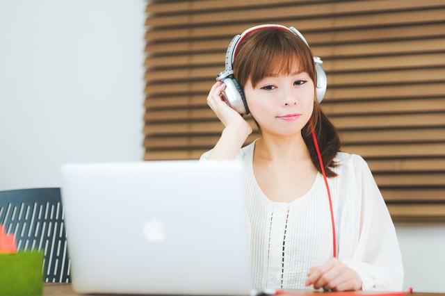 ヘッドフォンで音楽を聴きながらノマドする女性の写真