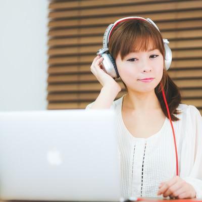「ヘッドフォンで音楽を聴きながらノマドする女性」の写真素材