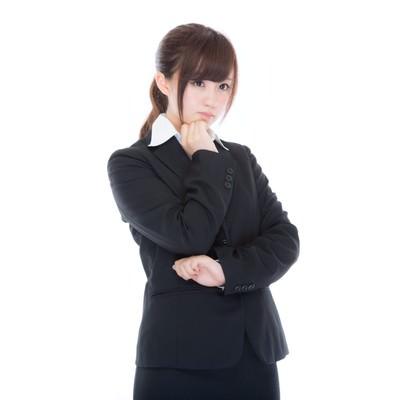 「考えこむスーツ姿の女性社員」の写真素材
