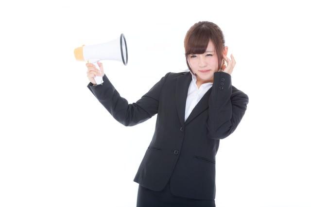 スピーカーがうるさくて嫌になる女性社員の写真
