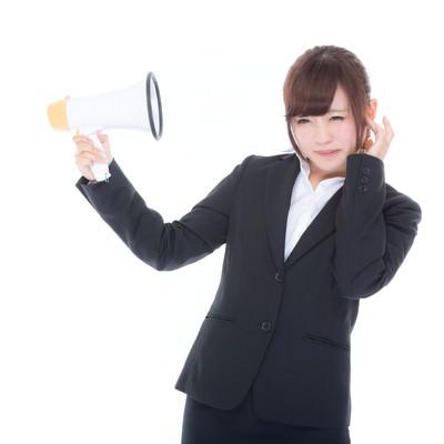 「スピーカーがうるさくて嫌になる女性社員」の写真素材