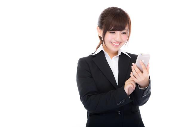 就業中にスマホから利益確定をするスーツ姿の女性の写真