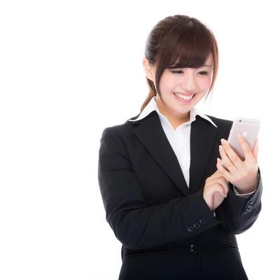 「就業中にスマホから利益確定をするスーツ姿の女性」の写真素材