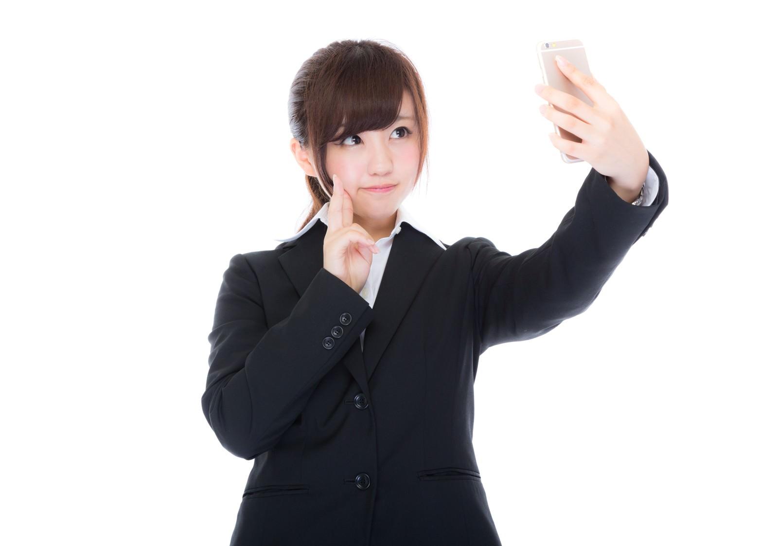 「自撮りをする女性の新入社員」の写真[モデル:河村友歌]
