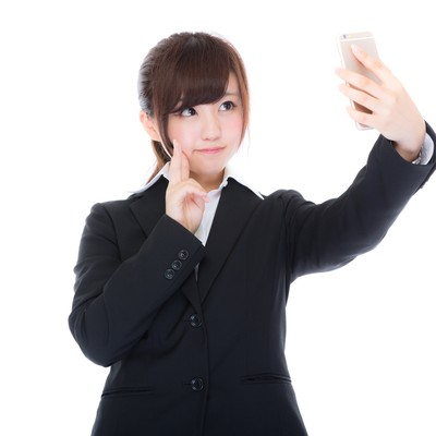 「自撮りをする女性の新入社員」の写真素材