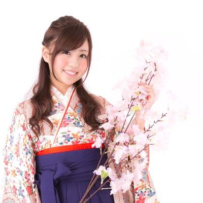 桜の枝と袴姿の女性の写真