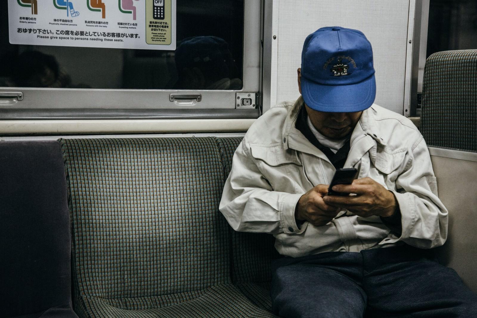 「ローカル線で帰宅する作業着姿の年配者」の写真