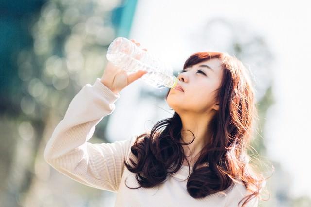 ミネラルウォーターを飲む若い女性の写真