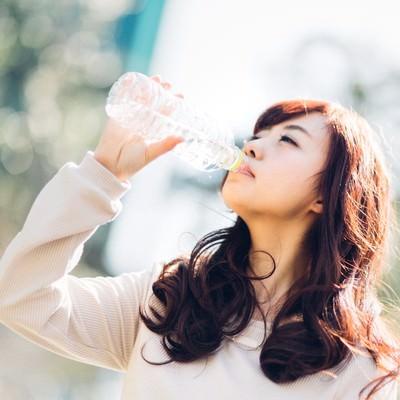 「ミネラルウォーターを飲む若い女性」の写真素材