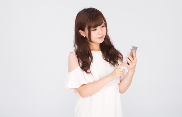 スマートフォンアプリを使うキラキラ女子の写真