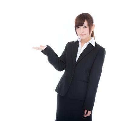 「ご案内するスーツ姿の受付け嬢」の写真素材