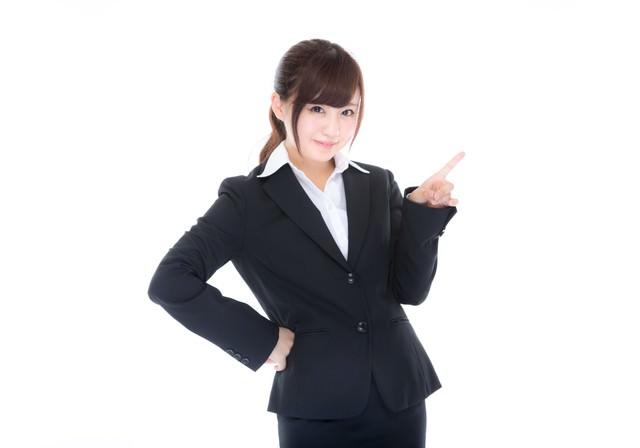 指をさしてご案内するスーツ姿の受付の写真