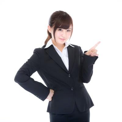 「指をさしてご案内するスーツ姿の受付」の写真素材