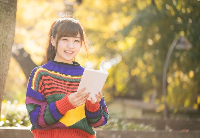 読書の秋、紅葉に包まれる80s風女子の写真