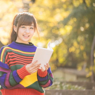 「読書の秋、紅葉に包まれる80s風女子」の写真素材