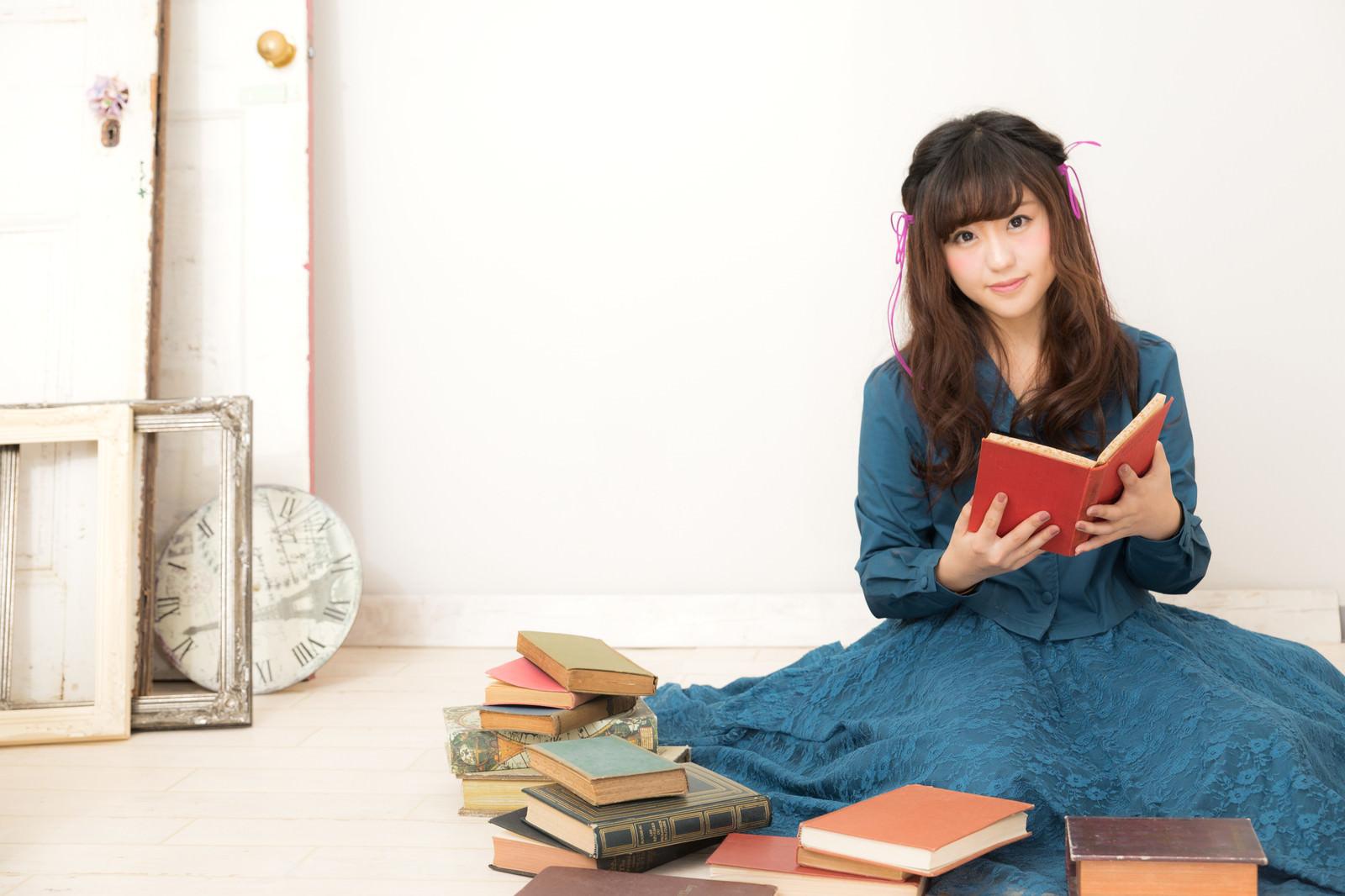 「本に囲まれるふんわり女子」の写真[モデル:河村友歌]