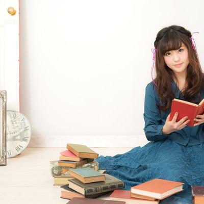 「本に囲まれるふんわり女子」の写真素材