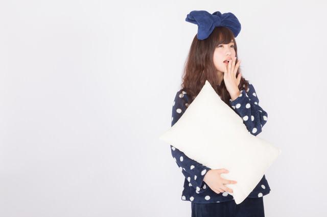 枕を抱えてあくびするパジャマ姿の女性の写真
