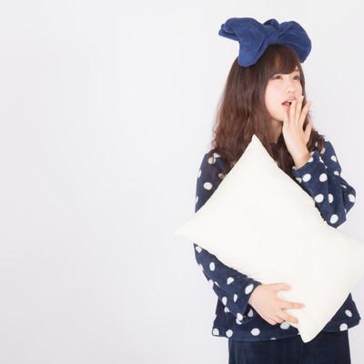 「枕を抱えてあくびするパジャマ姿の女性」の写真素材