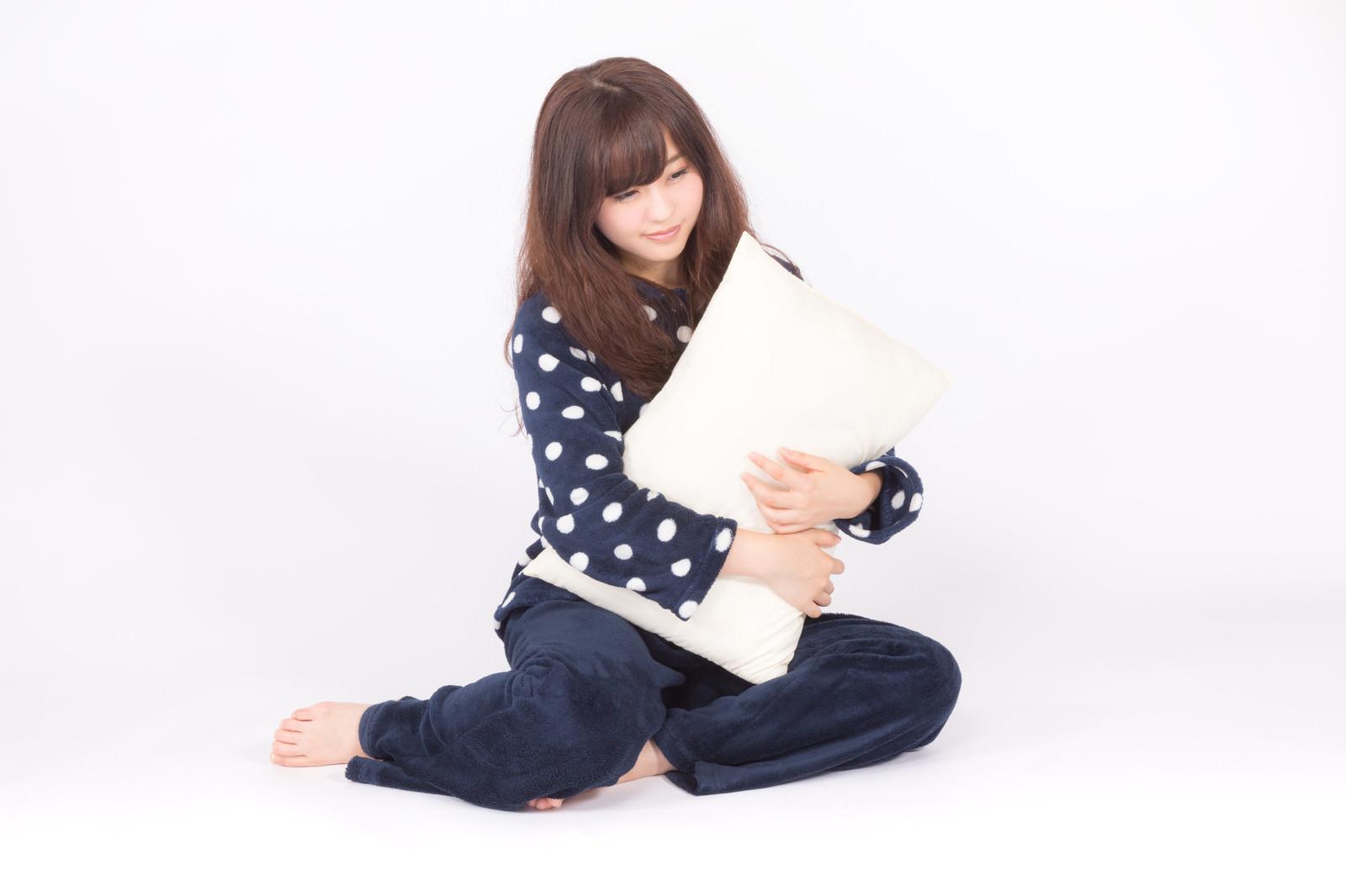 「枕を抱いて眠そうな表情の若いパジャマ姿の女性」の写真