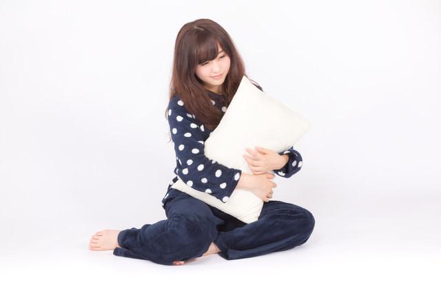 枕を抱いて眠そうな表情の若いパジャマ姿の女性の写真