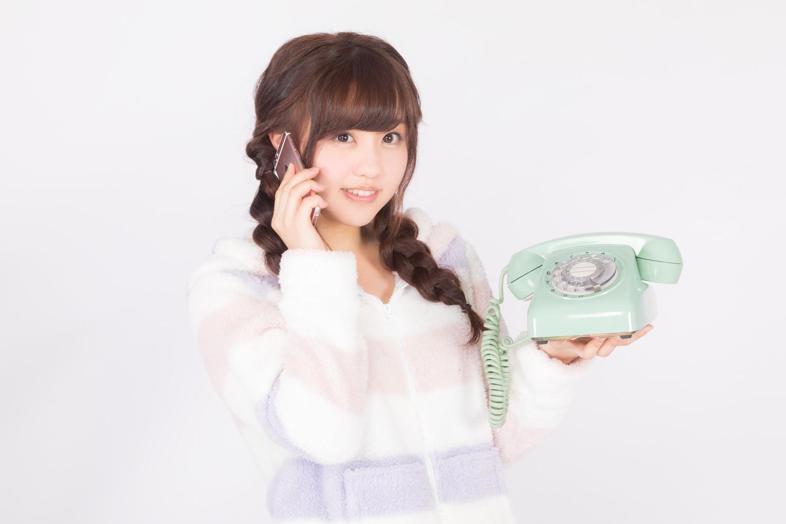 「ダイヤル式電話機の使い方がわからずスマホから電話する平成生まれ」の写真[モデル:河村友歌]