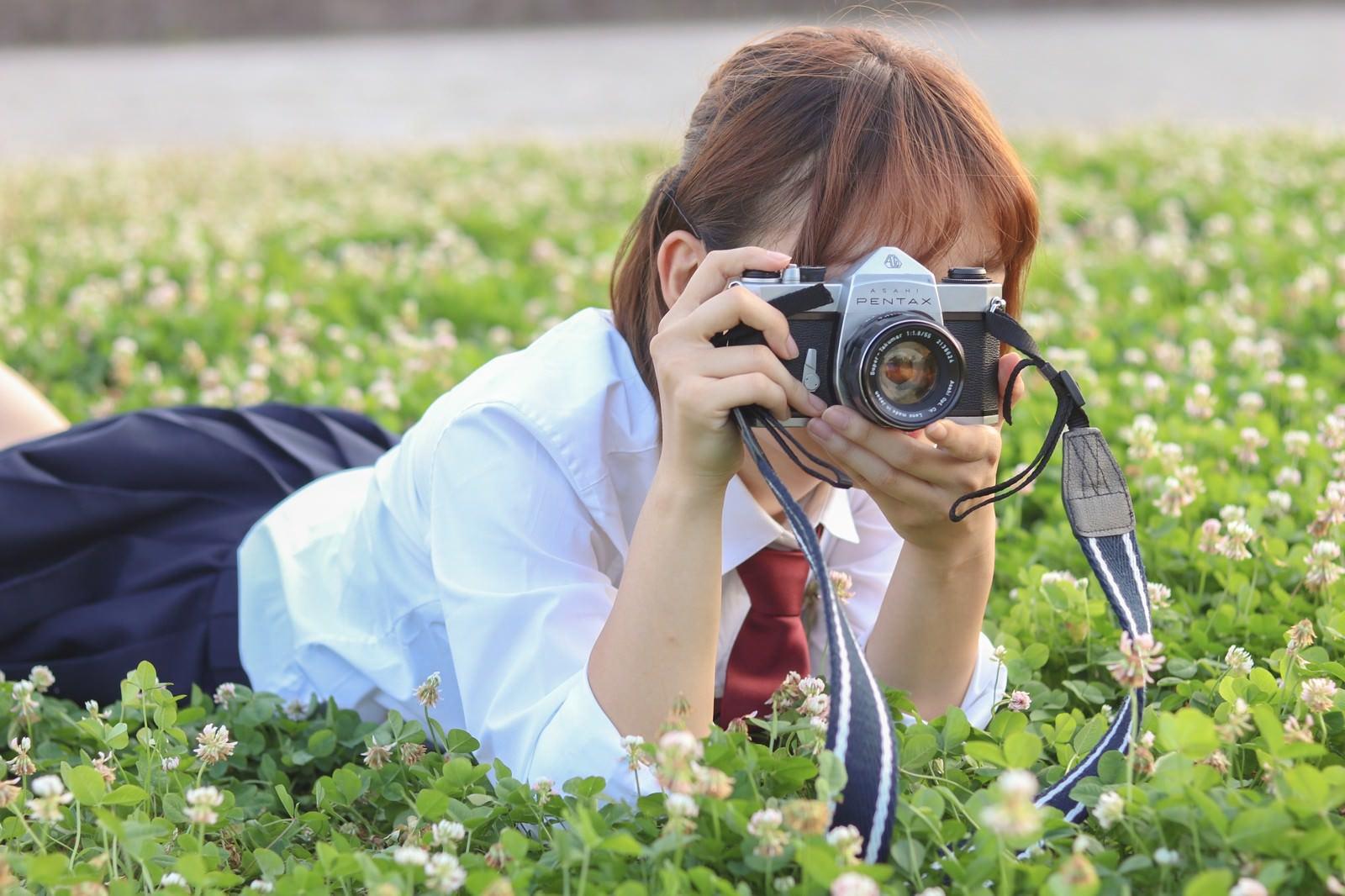 「草原にうつ伏せてカメラを構える女子高生」の写真