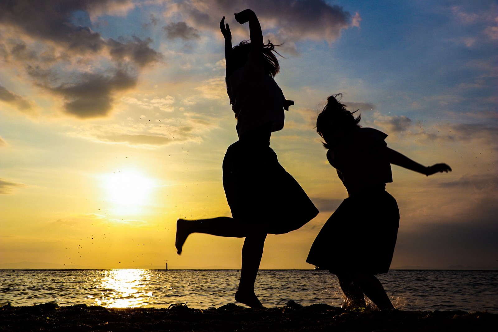 「焼けた空と浜辺で歓喜する二人のシルエット」の写真