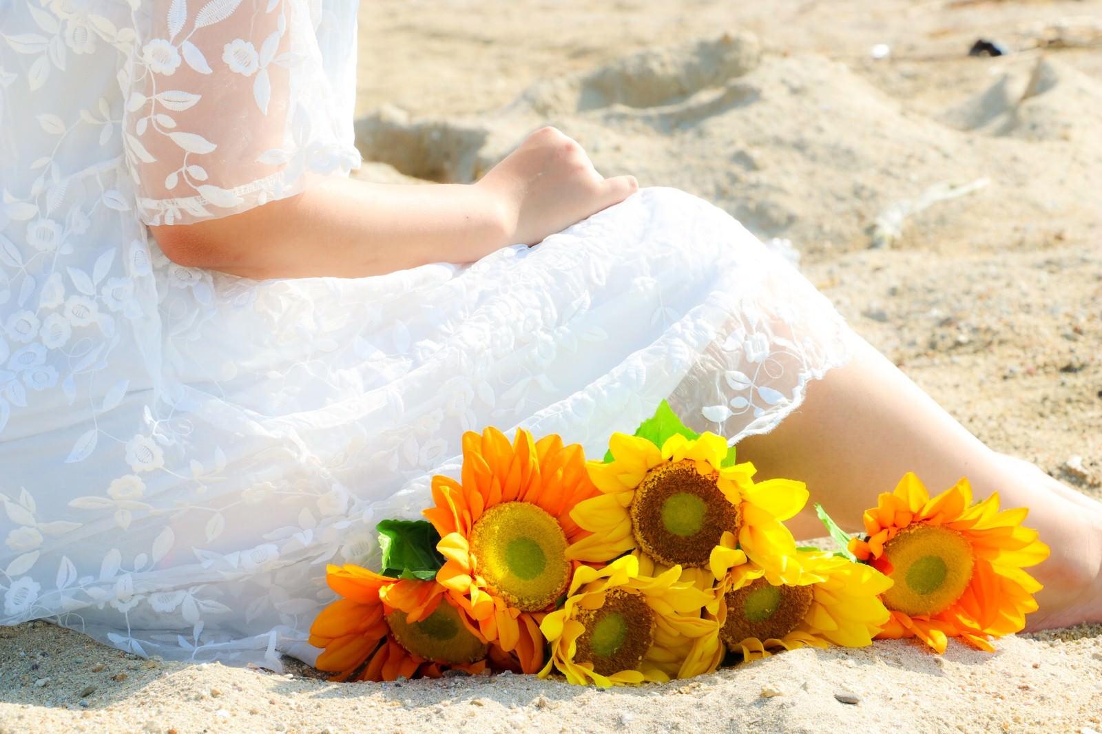 「砂浜で想い出に浸る女性」の写真