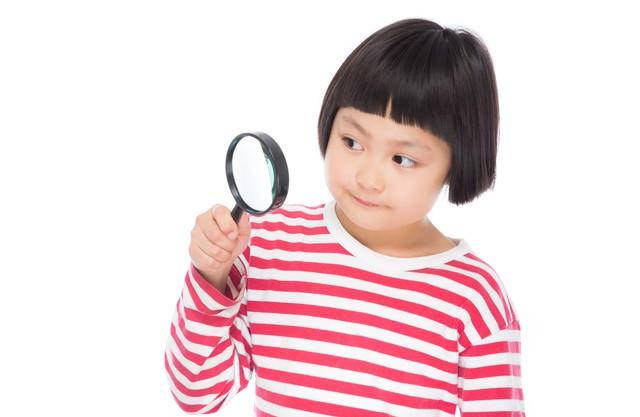 虫眼鏡で観察する小学生の写真
