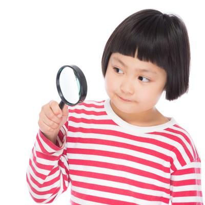 「虫眼鏡で観察する小学生」の写真素材