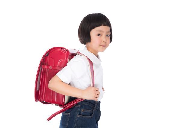 ランドセルを背負った小学生低学年の写真