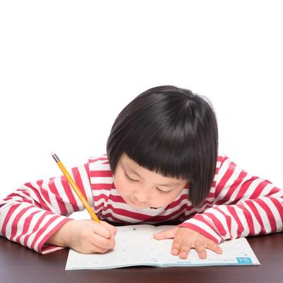「宿題をがんばる前髪パッツンの女の子」の写真素材