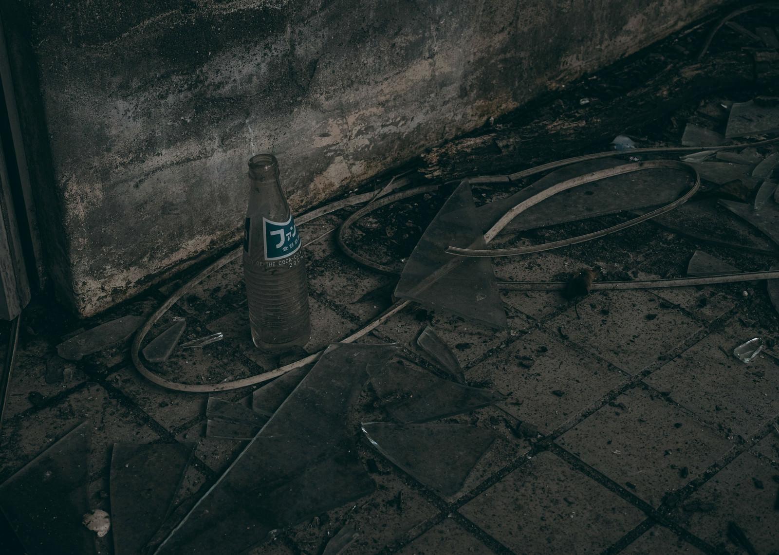 「ガラスが飛散るなか廃墟とジュースの空瓶」の写真
