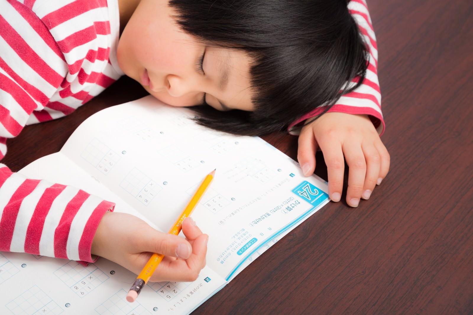 「宿題しながらスースーと寝息を立てる女の子」の写真[モデル:ゆうき]