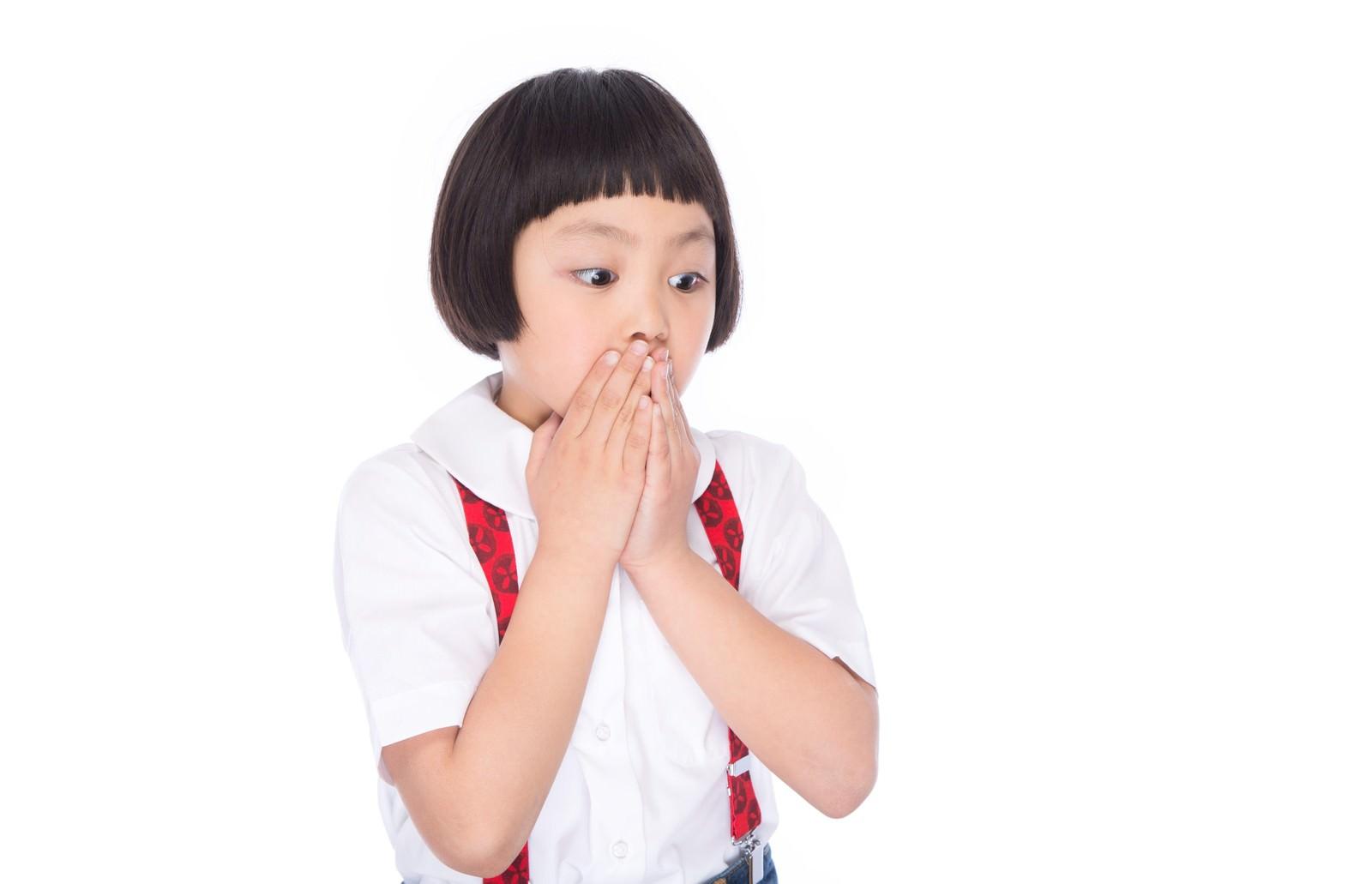 「両手で口を塞ぎ驚いた表情で何かを見つめる小さい女の子」の写真[モデル:ゆうき]