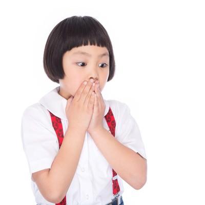 「両手で口を塞ぎ驚いた表情で何かを見つめる小さい女の子」の写真素材