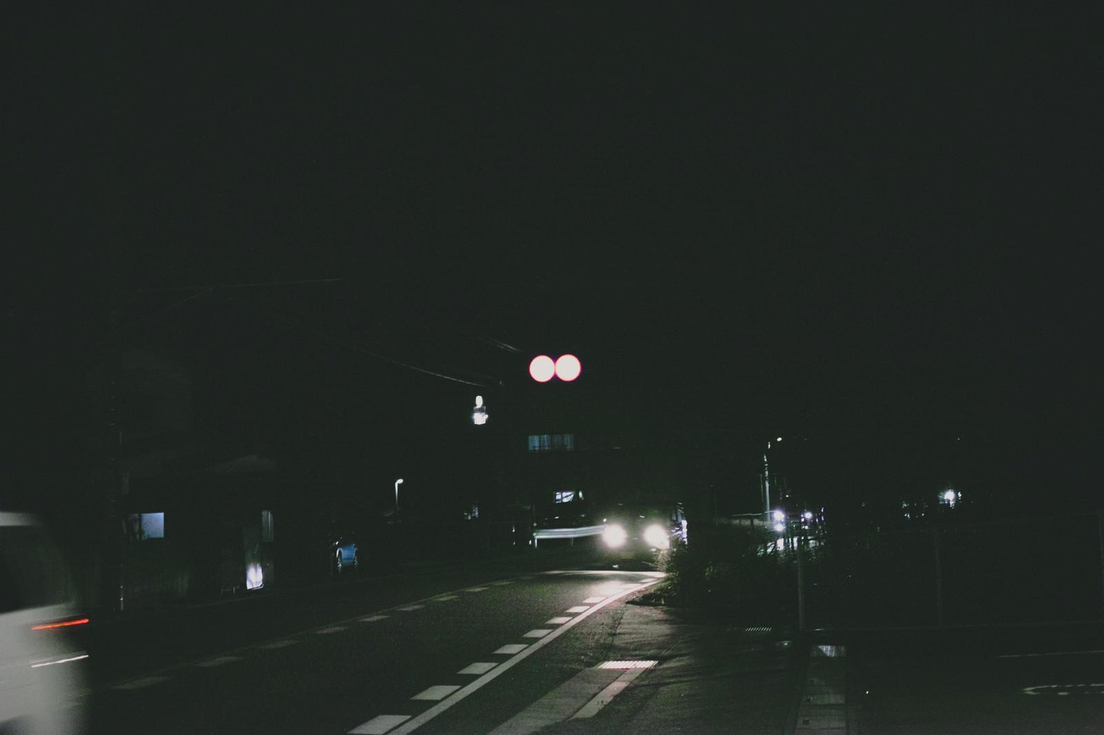 「夜間走行する車のヘッドライト」の写真