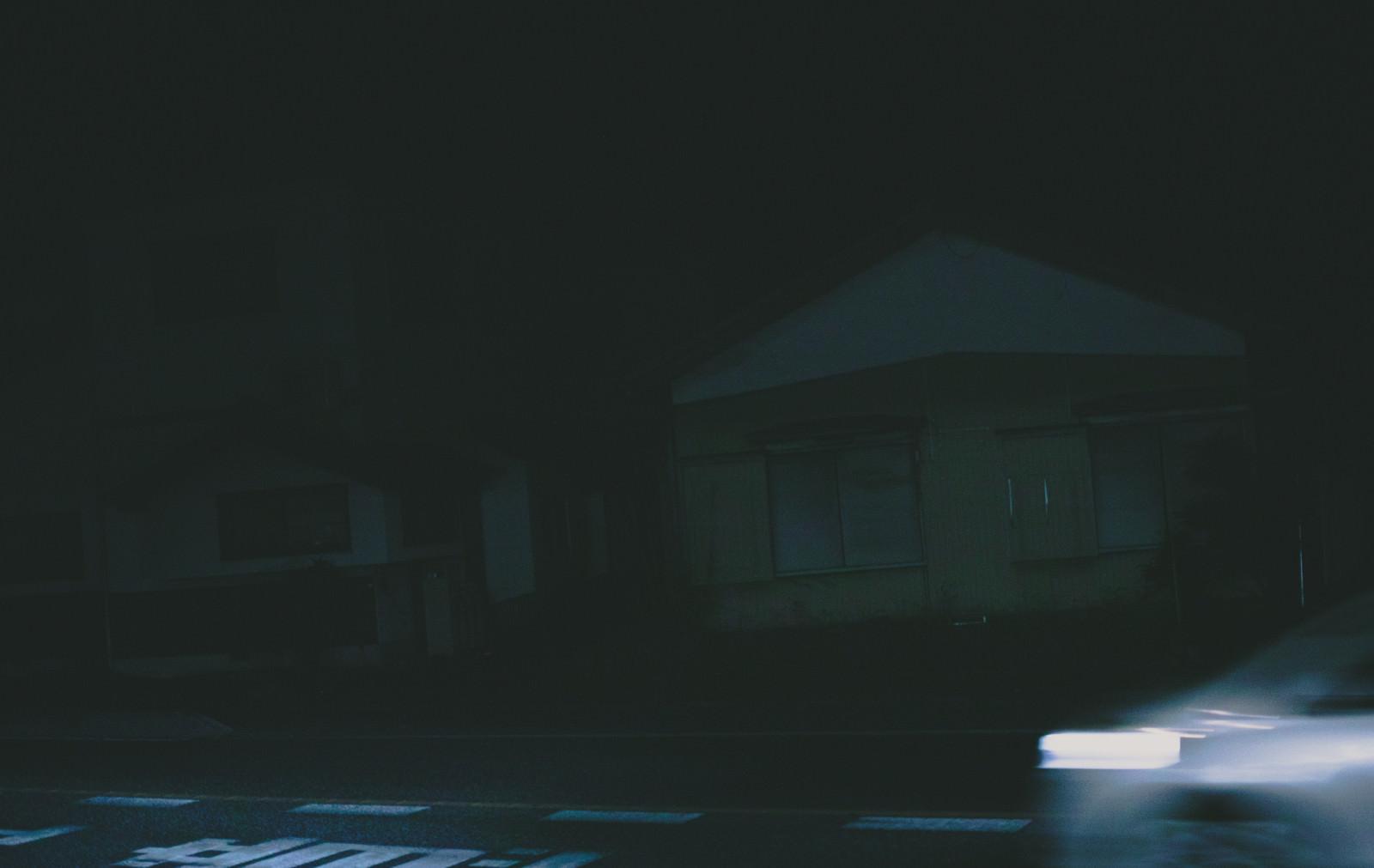 「深夜帯の民家前を走り去る車の残像」の写真