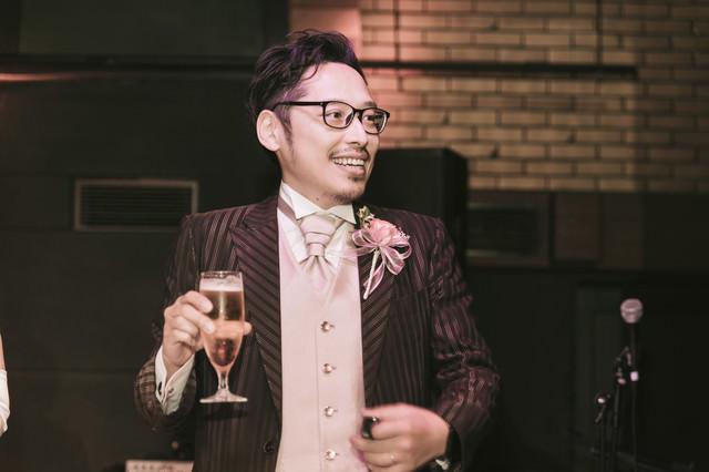 乾杯の挨拶でグラスを持つ新郎の写真