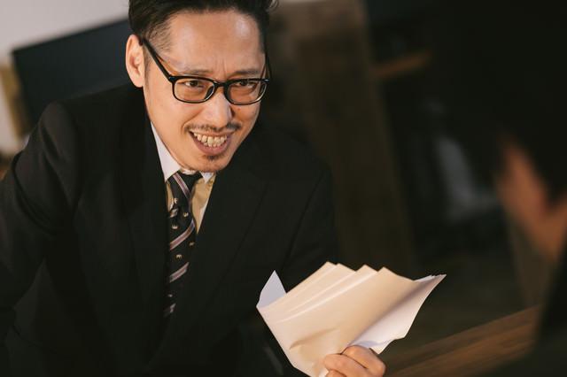 怪しい儲け話を持ちかけてくるスーツ姿の男性の写真