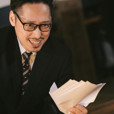 「怪しい儲け話を持ちかけてくるスーツ姿の男性」の写真素材
