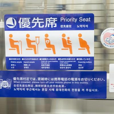 「優先席付近に貼られたマタニティマークとヘルプマーク」の写真素材
