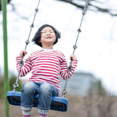 「公園のブランコではしゃぐ子供」の写真素材