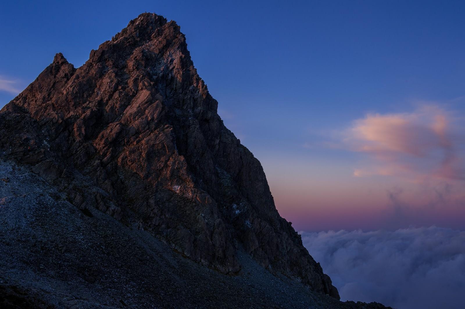 「日没後の残光に淡く照らされた槍ヶ岳」の写真