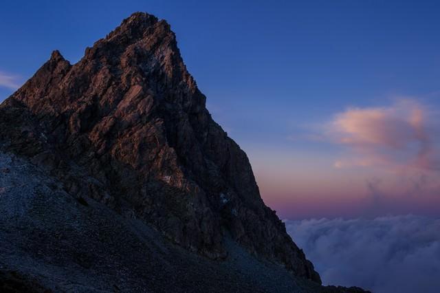 日没後の残光に淡く照らされた槍ヶ岳の写真