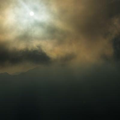 「ガス中の北アルプスから現れた月明かり」の写真素材