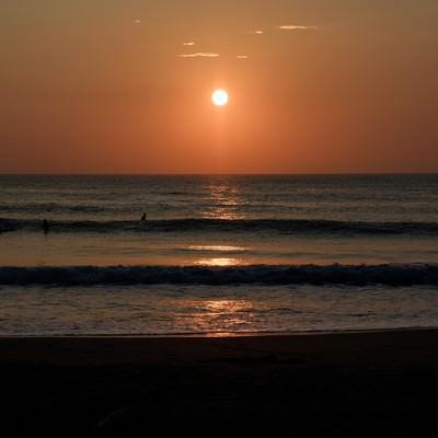 朝日を背に海岸に打ち寄せる波(千葉県一宮町)の写真