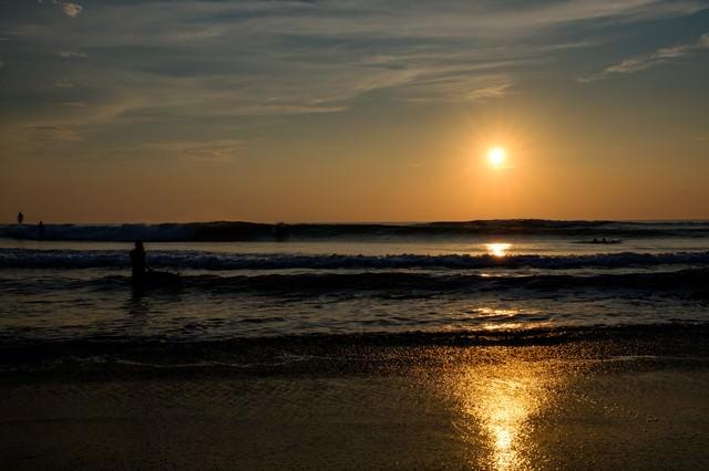 朝日を背に高波に挑むサーファー達(千葉県一宮町)の写真